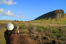 Young Female Tourist Taking Pictures Of Rano Raraku Volcano, Quarry Of Moai Statue In The Ancient Time Of Easter Island, Chile, South America