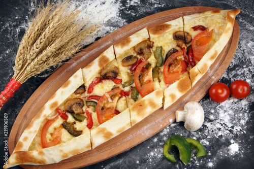 Fotografía  The national Turkish pizza is called pide, next to vegetables and spikelets of w