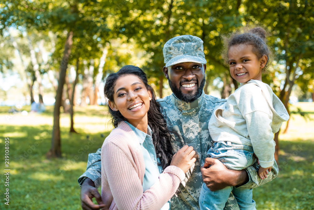 Fototapety, obrazy: happy african american soldier in military uniform looking at camera with family in park