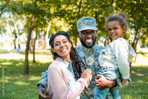 Fotografiet  happy african american soldier in military uniform looking at camera with family