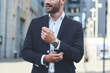 Confident Businessman. Cropped Shot Of Businessman In Stylish Suit Straightens The Sleeve