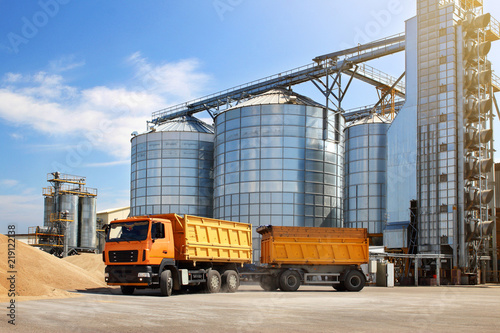 Agricultural silo truck of orange color on the territory of grain storage in sunny weather Slika na platnu