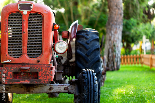 An old vintage red tractor near a farm field at sunset