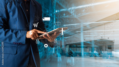 Fotografie, Obraz  Logistic and transport concept : Businessman manager using tablet check and control and planning for Modern Trade warehouse logistics