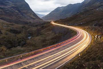 UK, Szkocja, lekkie ślady samochodów na malowniczej drodze przez góry w szkockich wyżynach w pobliżu Glencoe o zmierzchu