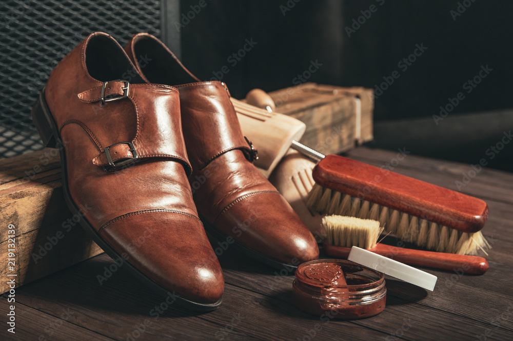 Fototapeta Leather shoes and shoe polish equipment on a wooden composition