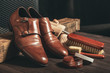 canvas print picture - Leather shoes and shoe polish equipment on a wooden composition