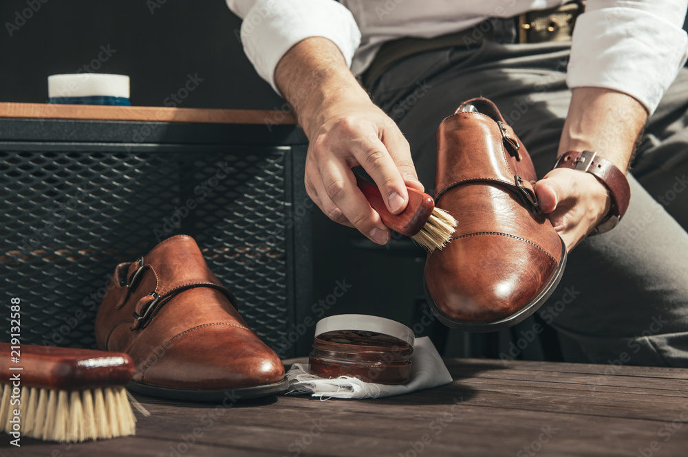 Fototapeta Man applies shoe polish with a small brush