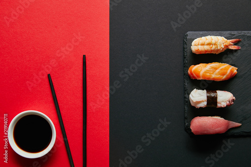Tuinposter Sushi bar flat lay with soya sauce in bowl, chopsticks and nigiri sushi set on black slate plate on red and black background