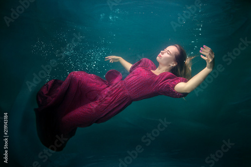Photo  Woman in a red dress is underwater, she is sleeping.