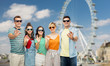 travel, tourism and entertainment concept - group of happy smiling friends in sunglasses showing ok hand sign over ferry wheel in london background