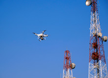 White Drone Flying In City Near Telecommunication Tower