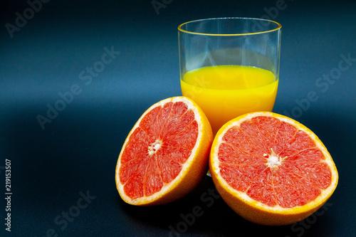 Fotografie, Obraz  arancia o pompelmo vicino ad un bicchiere di succo d'arancia su sfondo nero