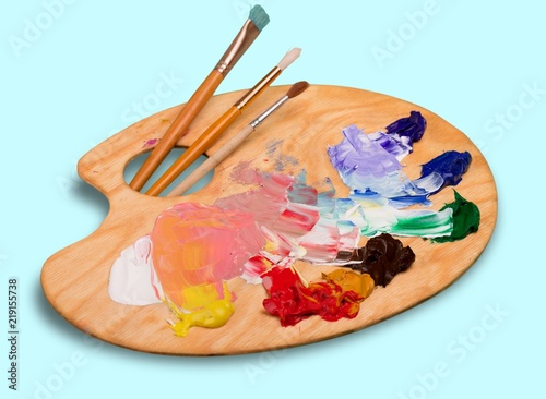 Cuadros en Lienzo Wooden art palette with blobs of paint and a brushes on white