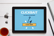 Clickbait concept on tablet screen with office objects on white wooden table. All screen content is designed by me. Flat lay