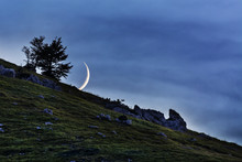 A Waxing Crescent Moon Over The Mountain