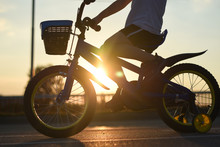 Little Boy Riding Bike At Sunset. Child On Bicycle Into The Sun