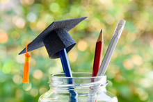 Education And Knowledge Is Important For Student And Most Powerful Weapon Concept : Black Graduation Cap Or Hat On Pencil In Bottle, Depicts The Power Of Success In Education. Green Nature Background.