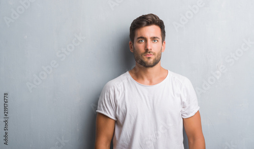 Fotografiet  Handsome young man over grey grunge wall with serious expression on face