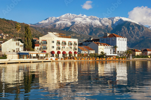 Foto op Canvas Nachtblauw Sunny winter Mediterranean landscape. Montenegro, embankment of Tivat city and snow-capped peaks of Lovcen mountain