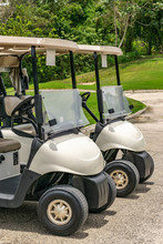 Two Empty White Golf Carts Parked Beside Each Other On The Driveway Of A Golf Course In Montego Bay, Jamaica