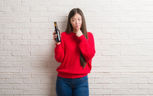 Young Chinese Woman Over Brick Wall Drinking Beer Serious Face Thinking About Question, Very Confused Idea