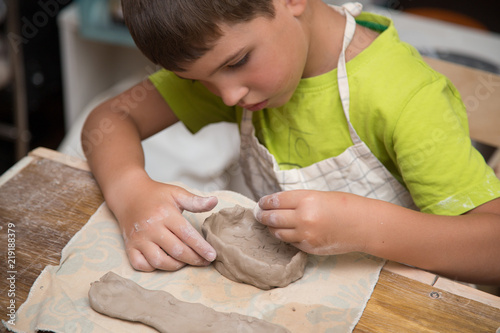 Fototapeta Pottery workshop for kids, raw clay, sculpting tools, glazing and painting clay