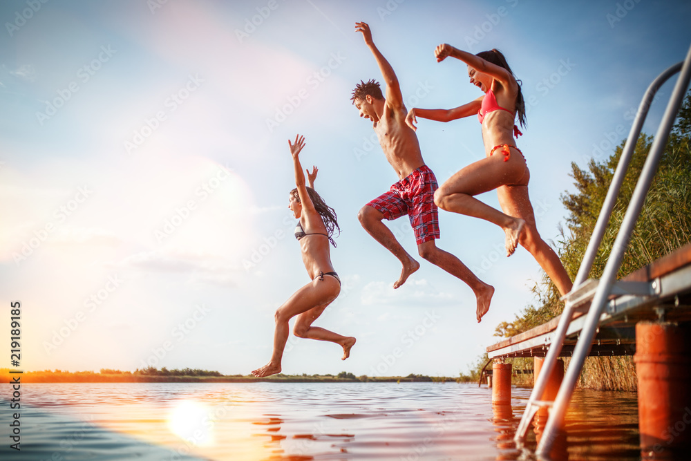 Fototapety, obrazy: Group of friends jumping into the lake from wooden pier.Having fun on summer day.