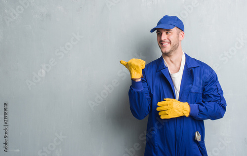Fotomural Young caucasian man over grey grunge wall wearing mechanic uniform pointing and
