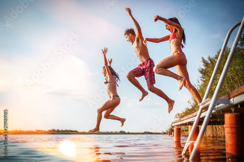 Obraz Group of friends jumping into the lake from wooden pier.Having fun on summer day. - fototapety do salonu