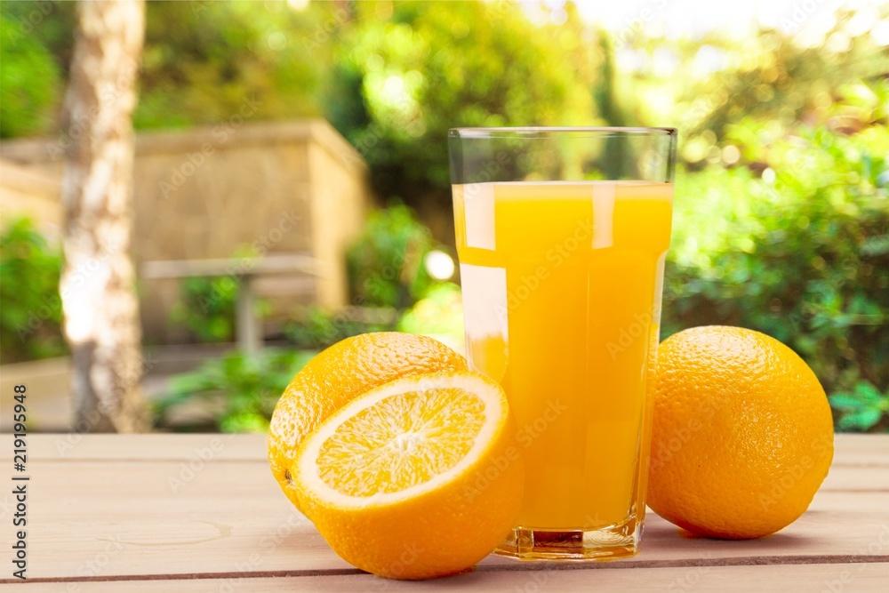 Fototapeta Orange juice and slices of orange on background