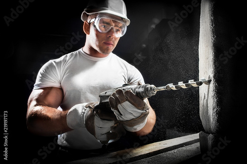 Fotografia Young man using electric drill on white brick wall in a white helmet