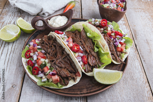 Mexican tacos with roasted beef ,sauce and salsa tomato