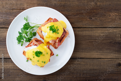 Photo Eggs benedict with bacon on wooden background . Top view