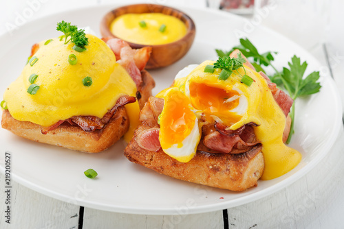 Eggs benedict with bacon on white  wooden background . Canvas Print