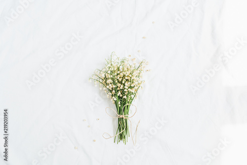 Foto op Canvas Lelietje van dalen Lily of the valley flowers bouquet on white background. Flat lay, top view minimal floral concept.