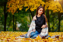 A Beautiful Girl Took Refuge In A Blanket In The Autumn Park, A Sweet Girl In Nature In October In Yellow Leaves