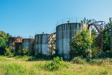 Old Rusty Abandoned Oil Tanks With Stairs Overgrown By Trees