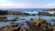 View of a puddle of sea water at low tide on the basalt rocks and the blue ocean in the background. Slow motion panoramic