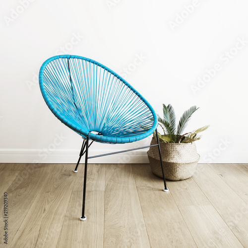 Fotografia, Obraz Close up shot of a light blue acapulco chair on white wall