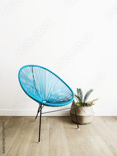 Fotografija  Close up shot of a light blue acapulco chair on white wall