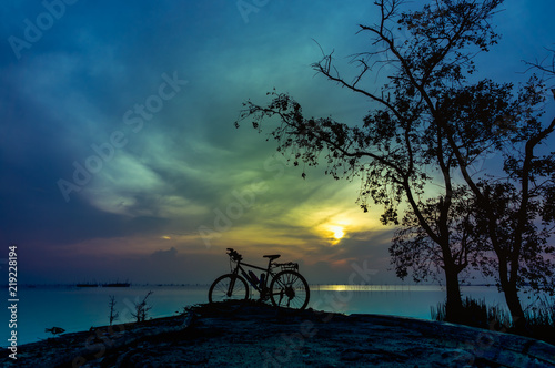 Canvas Prints Autumn Silhouette of bicycle on the beach against colorful sunrise in the morning.