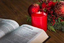 Bible Next To Candles And Christmas Greenery
