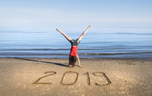 New Year 2019 Written On The Sand And A Girl Jumping On The Beach