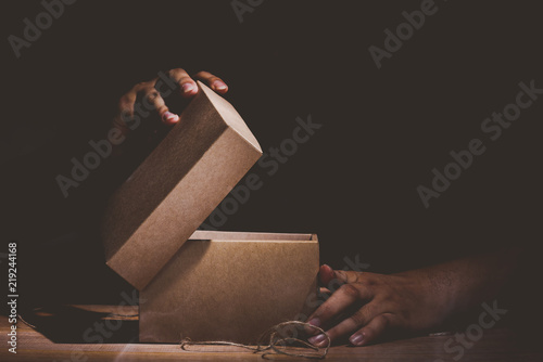 Fototapeta hand hold and open a mysterious box on wooden table obraz