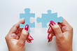 Female hands hold two elements of a puzzle piece on a white background.