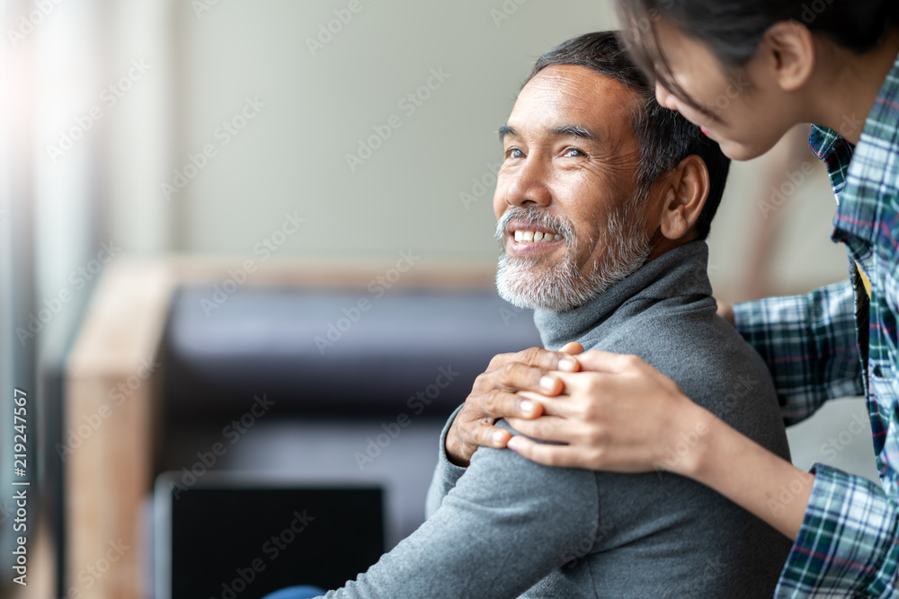 Fototapeta Smiling happy older asian father with stylish short beard touching daughter's hand on shoulder looking and talking together with love and care. Family relationship with bond and care concept.