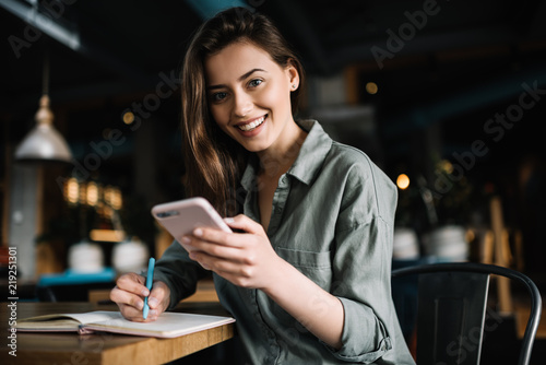 Obraz Cheerful female using mobile phone for online banking, shopping web, learning  language sitting in loft coffee shop.   Positive caucasian woman holding modern smartphone  and making notes to study.  - fototapety do salonu