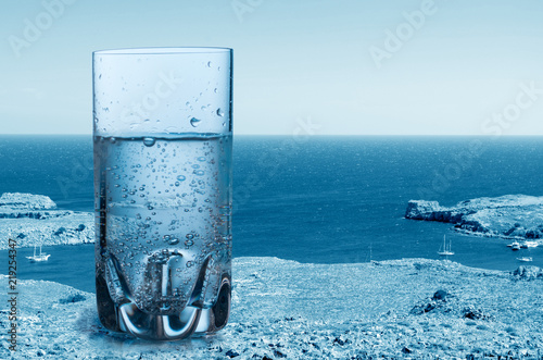 Cuadros en Lienzo Glass of sparkling pure water against the sea background