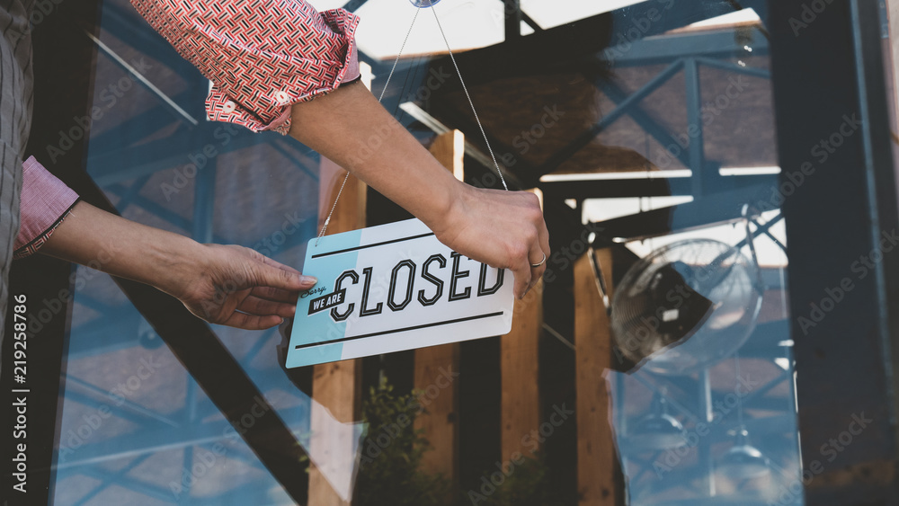 Fototapeta Caucasian female turning sign from open to closed on the entrance door of his small cafe. Out of business